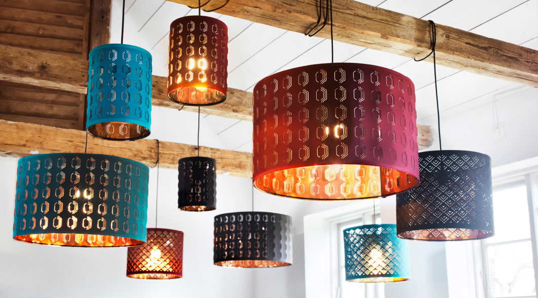 An assortment of lamps and lampshades hanging from wooden beams in a bright lit room
