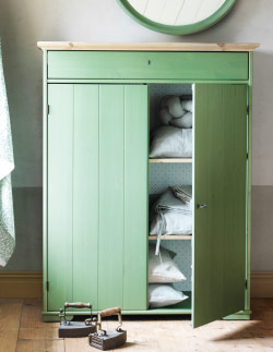Green linen cabinet with one door open revealing linen fabrics