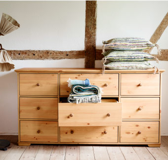 Brown chest of drawers with fabric spilling out of center drawer