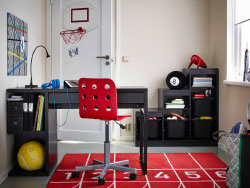 A kids' room with a brown MICKE desk, a red JULES chair and TROFAST storage in black