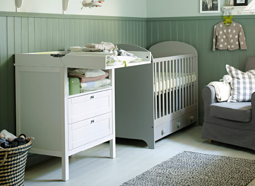 Changing table and cot side by side, placed next to a couch