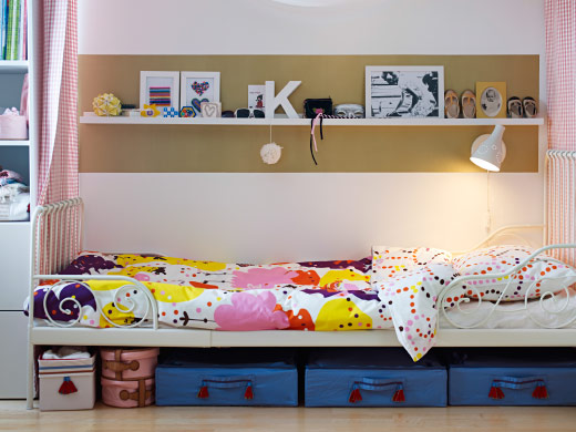 Child's bed with colourful printed quilt cover and pillow, a shelf, lamp,  and underbed storage