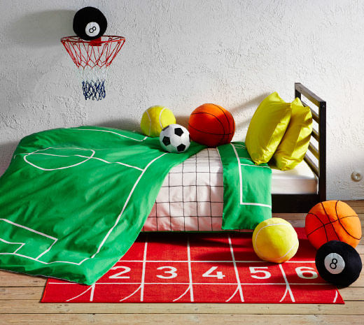 View of child bed with sport themed textile and rug and assorted toys