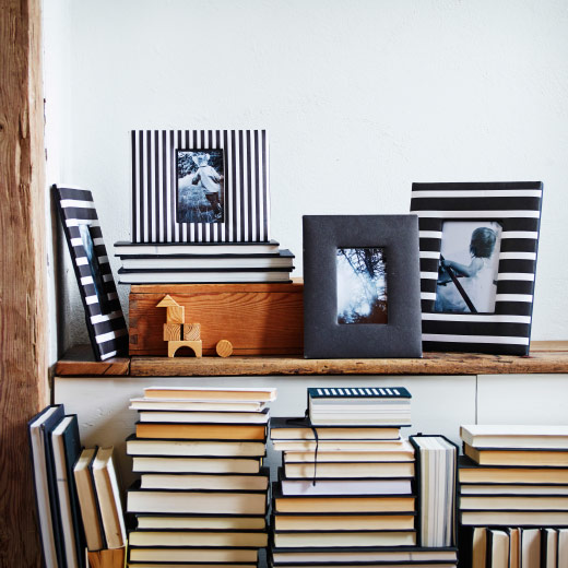 Picture frames set on a shelf above some stacked books