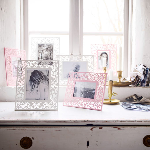 Picture frames on a dresser against a brightly sunlit window