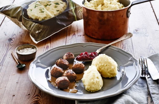 Plate of mashed potatoes and meatballs with package of frozen mashed potatoes in background