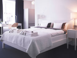 A hotel room in white with a bed for two, bedside tables and a desk