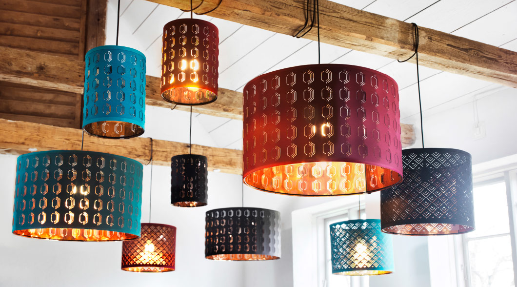 An assortment of lamps and lampshades hanging from wooden beams in a brightly lit room