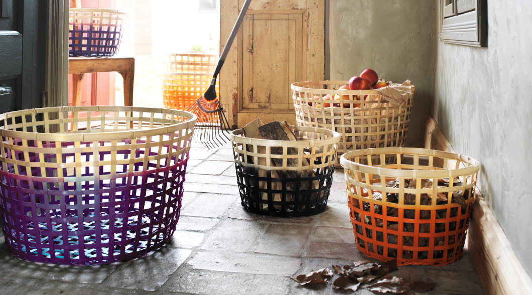 Assortment of seasonal coloured bamboo baskets of various sizes, with bright sunlight shining in from an open doorway