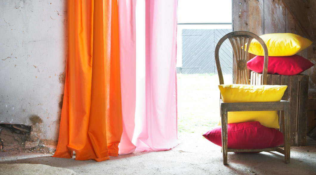 Colourful pillows and a two-toned curtain bathe in bright sunlight from an open door