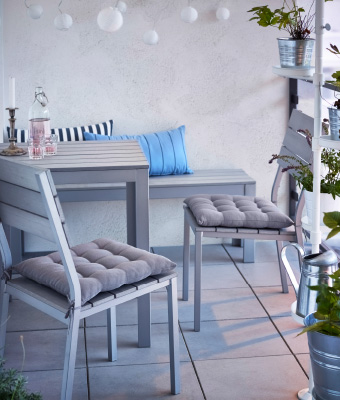A small balcony with grey shelving units filled with green plants, a round table and a plastic rattan armchair