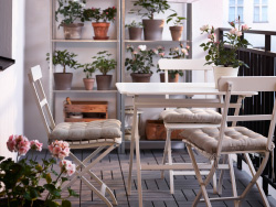 A balcony with white folding chairs and table together with shelving units in galvanised steel