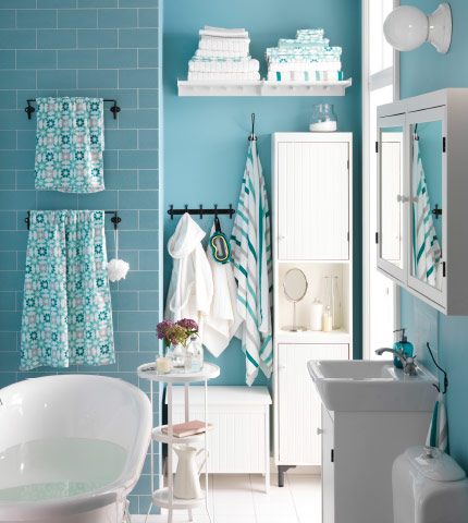 Calm, green-toned bathroom with an  assortment of towels on a shelf and hanging from towel racks and hooks