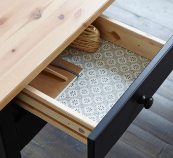 Open desk drawer revealing classical print inner lining