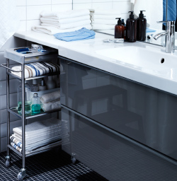 Close-up view of an IKEA wash-stand with bathroom trolley on either side holding toiletries and towels.