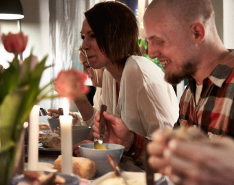 Close-up of people eating dinner around a table in a small space.