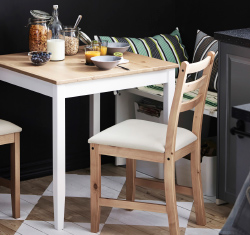 Small IKEA table with two chairs, laid for breakfast, in the corner of a kitchen.