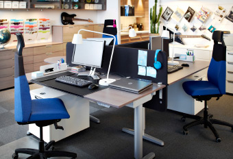 An office with electrically adjustable desks in ash veneer/silver-colour