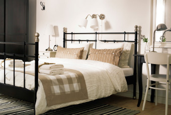 A B&B guest room with a black bed and beige/white bed textiles
