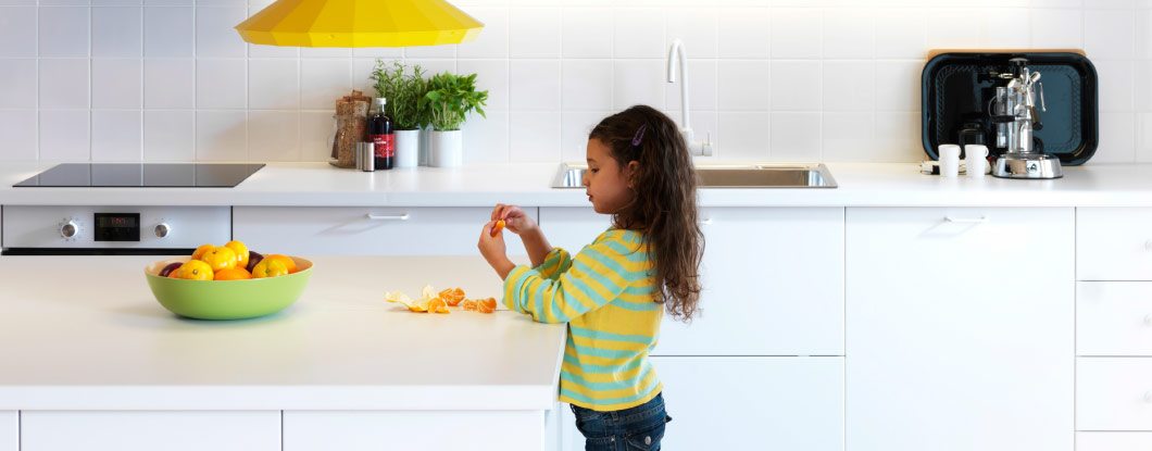 A young girl peeling an orange in a white IKEA kitchen.