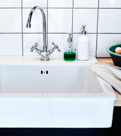 A close up of a white, porcelain IKEA sink with an IKEA stainless steel tap with wood worktops either side and soap inpump-dispensers on one side of the taps.