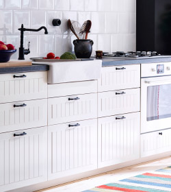 A kitchen worktop with an oven, a sink and tap with white drawers and cupboards below.