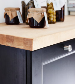 A close up of a wooden IKEA kitchen benchtop with jars of pickled goods and jams on top.