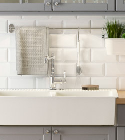A close up of a white, porcelain IKEA sink in a gray kitchen.