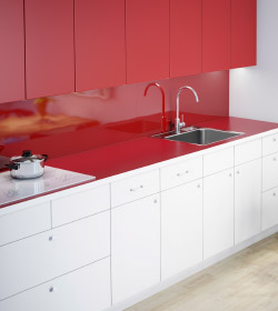 A view of a kitchen with white base cabinet fronts and red wall cabinets, red wall panels and a red worktop.