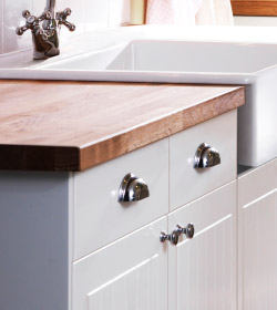 A close up of a wooden IKEA kitchen countertops with white base cabinets below.