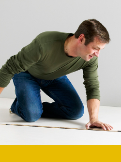 A man using a tape measure to measure a wall inside a room.