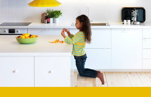 A young girl peeling an orange in a white, modern kitchen.