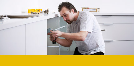 A man installing white kitchen base cabinets.