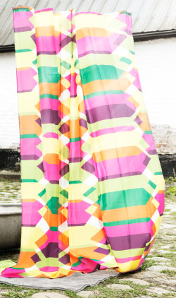 A bright multi-coloured shower curtain hanging outside in a courtyard