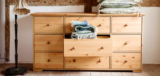 Front view of solid pine chest of drawers, with center drawer open revealing