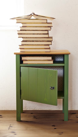 Books stacked on top of bedside table, with door slightly ajar.