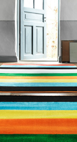 Multi-coloured rug leading to open door framed by sunlight