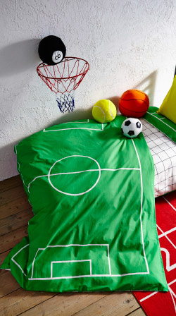 Sports themed textile with toys on it drapped over child's bed with rug on wooden floor