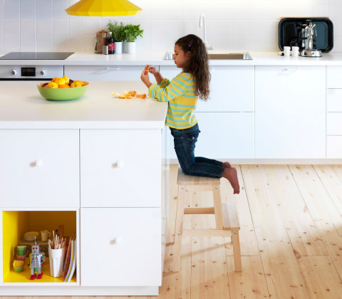 A child kneeling on a step-stool peeling an orange in a modern, white IKEA kitchen with wood floors and a yellow lamp.