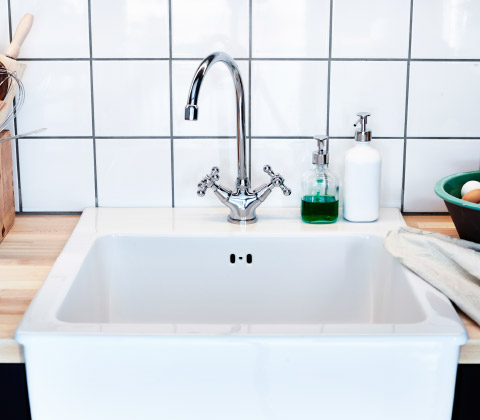A close up of a white, porcelain IKEA sink with an IKEA stainless steel mixer tap.