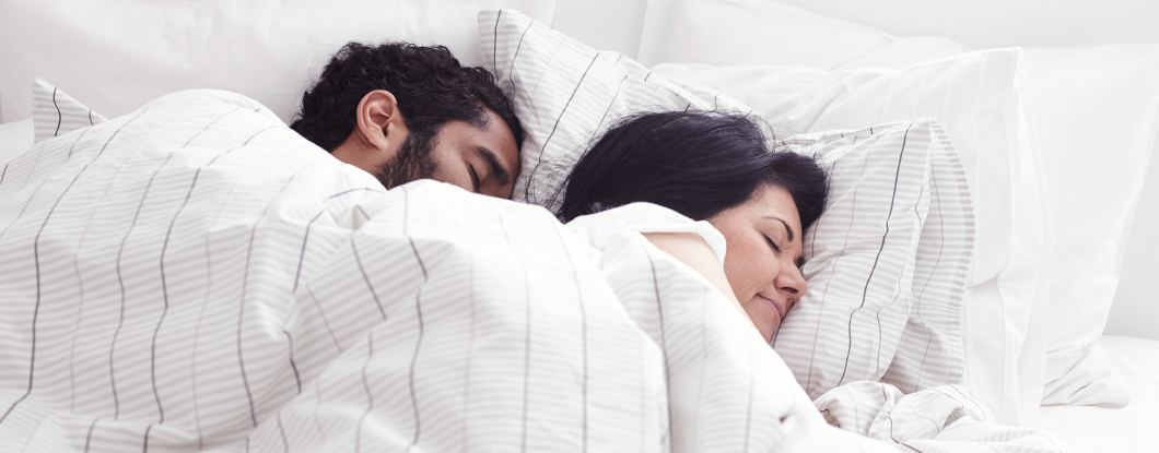 A male and a female asleep next to each other in a double bed with white bed linen.