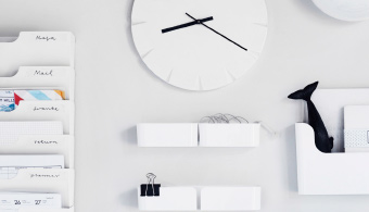 A selection of white storage products including a mirrored storage cabinet and a wall-mounted filing rack, a clock and light on a white wall with homely accessories for decoration.
