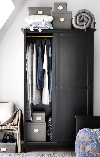 View of a reach-in closet space with sliding doors and IKEA furniture and fittings.