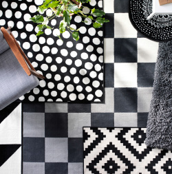A bird's eye view of layers of black and white rugs in different textures and with different patterns on the floor or a living room.