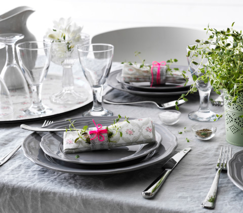 A set table with a grey table cloth, grey plates, napkins, glasses, cutlery and a green edible plant.