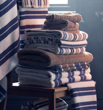 A close up image of a pile of striped and plain bathroom towels on a chair.