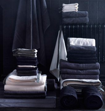 A close up image of a pile of black and white towels in a black tiled bathroom.