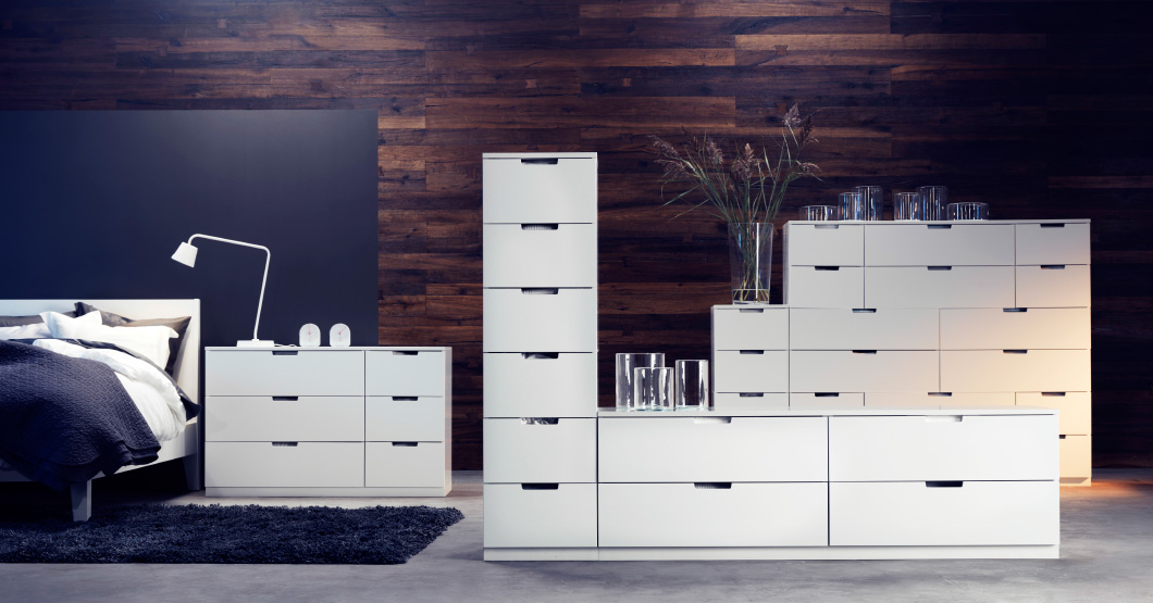 display of white bedroom storage against a wood panelled wall with a ...