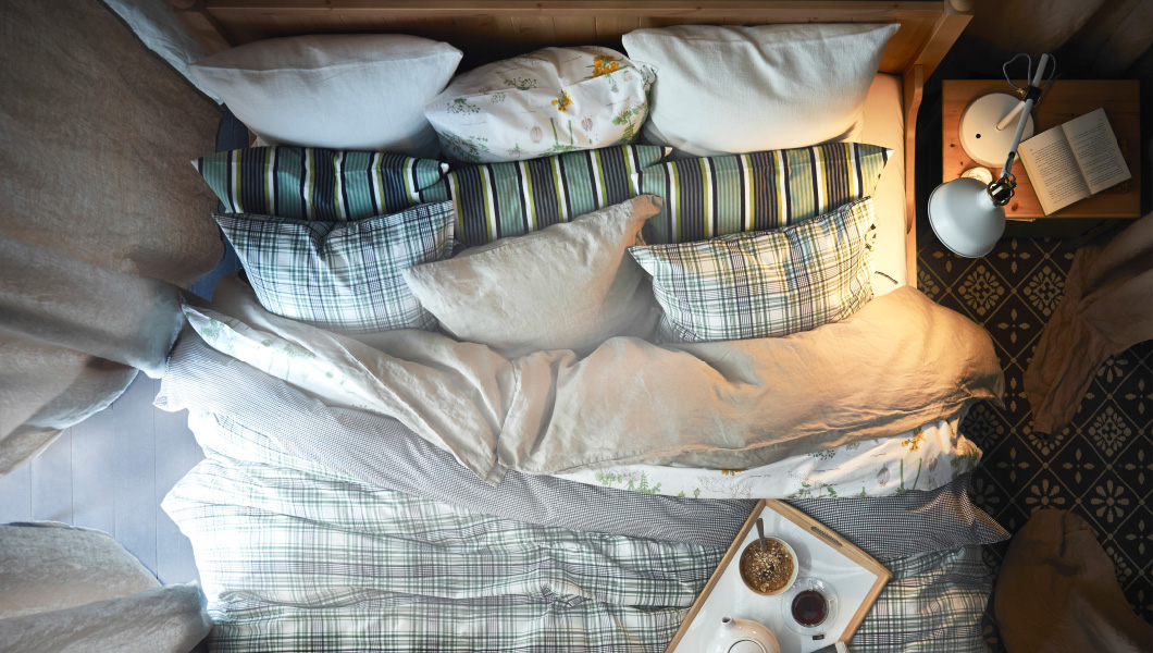 A bird's eye view of a bed made up with lots of pillows and thick, soft bedding.