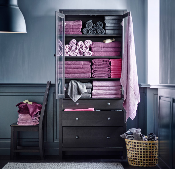 A cupboard opened to reveal lots of folded and rolled towles in shades of purple and grey in a grey painted hallway.